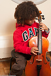 Education elementary Kindergarten music enrichment  male student playing cello learning to pluck strings in private music lesson