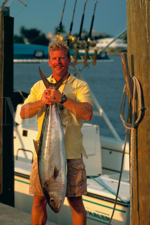 Happy fisherman holding freshly caught amberjack fish.