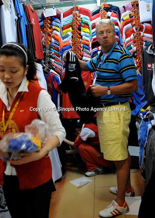 """Fake football shirts at the Silk Market. The """"Silk Market"""" in Central Beijing is proving a major tourist attraction with thousands of Olympic tourists flocking there daily in order to purchase fake designer goods ranging from clothing to watches.  The Beijing authorities closed hundreds of night-clubs and introduced many restriction on and rules ahead of the 2008 Olympics in the city mysteriously has allowed the trade of fake goods to foreigners continue, thumbing their nose at western companies.<br /> <br /> Photo by Richard Jones / sinopix"""