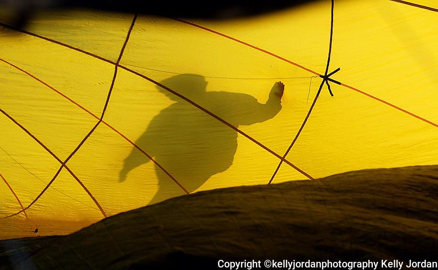 Balloon pilot Doug Gantt prepares his hot air balloon for flight as the sun rises over the DeLand airport Sunday morning, January 25, 2004.(Kelly Jordan)..**FOR MORRIS SULLIVAN STORY**