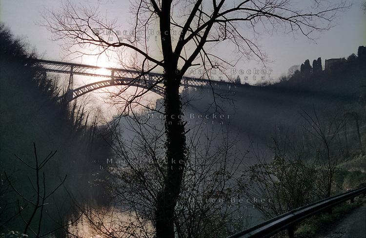 Il fiume Adda presso il ponte ad arco in ferro di San Michele a Paderno d'Adda (Lecco), avvolto nella nebbia --- The river Adda near the iron arch bridge of San Michele in Paderno d'Adda (Lecco), shrouded in mist