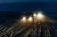 Four wheeling SUV's on the beach at dusk, Outer Banks, North Carolina, USA