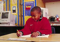 STUDENT WRITING AT HIS DESK. ELEMENTARY STUDENTS. OAKLAND CALIFORNIA USA CARL MUNCK ELEMENTARY SCHOOL.
