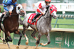 Headache with Miguel Mena (red cap) duels with Northern Giant and Shaun Bridgmohan as the field passes the stands for the first time in the 9th race at Churchill Downs. 05.21.2011