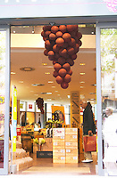 The entrance from the street with a giant bunch of grapes made from balloons. A man looking at wines on display. The Lavinia wine shop in Paris. Probably the biggest wine shop in Paris, with its special temperature controlled section for wines that are fragile and must be stored at cool low temperature.