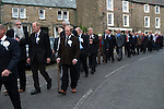 Askrigg Equitable Benevolent and Friendly Society. Askrigg north Yorkshire UK. The annual walk to church behind the Friendly Society banner starts from outside the Kings Arms Hotel. Honorary members wear white rosettes while ordinary members wear blue, and follow behind them.