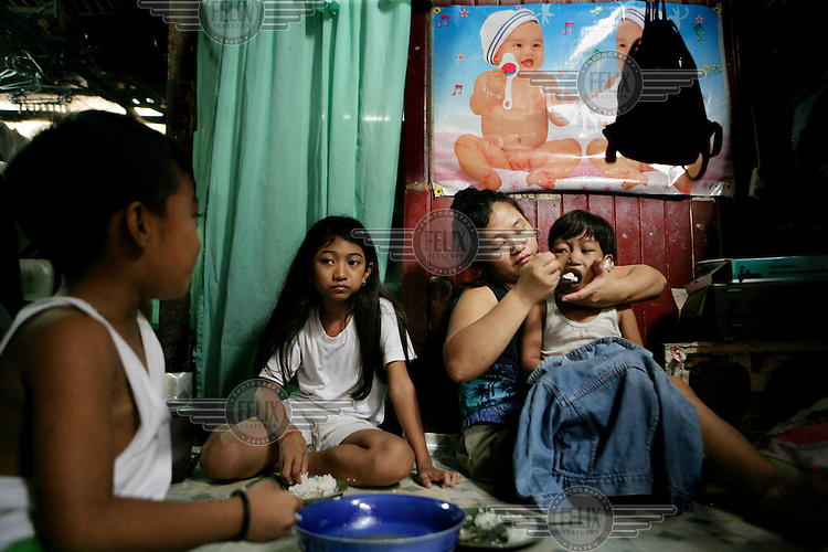 The Colandog family eats dinner at their home in the Santo Nino shanty town in Manila. People in this area live in small homemade huts, many made entirely from rubbish and leftover building materials that they found on the nearby garbage dump. These houses are all illegal, since no one has the acquired permissions to live on the land. People have been living here for up to twenty years - but everyday they might get moved and their neighbourhood demolished to make room for new apartment blocks that they could never afford to buy.