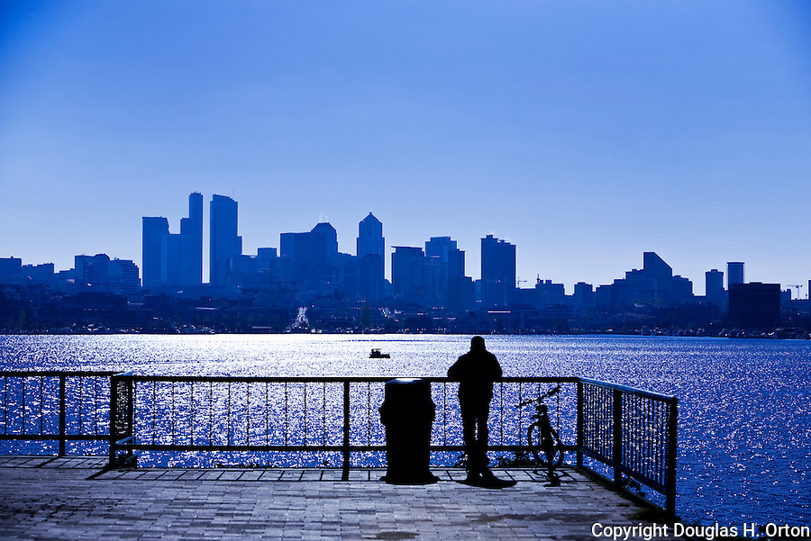Man looking across Lake Union toward the downtown Seattle skyline from Gasworks Park, a Seattle City Park at the north end of Lake Union on Northlake Way.