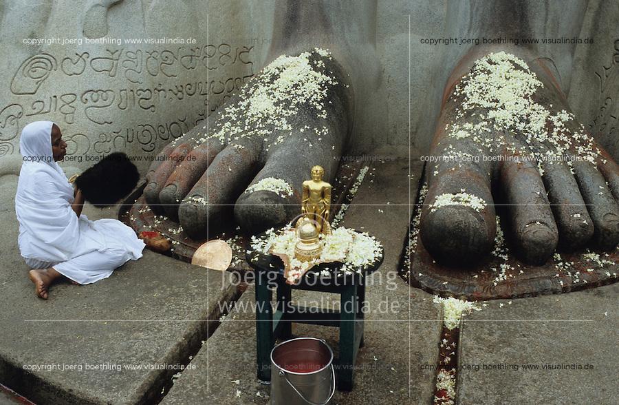 INDIEN Karnataka, Jain Nonne beim Gebet am Jainheiligtum Bahubali eine 17 Meter hohe Statue aus Granit des Jain Heiligen Lord Bahubali oder Gommata oder Gomateshvara in Shravana Belagola , Jains praktizieren als oberstes Gebot Gewaltverzicht ahimsa und sind strikte Vegetarier und lehnen das Kastensystem ab - Religion Jainismus als Reformbewegung aus Hinduismus hervorgegangen / INDIA Shravana Belagola Karnataka , Jain nun at Jain statue Bahubali