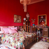A bold red bedroom with a double bed with a patchwork quilt and pink cushions. A wooden desk and chair stand against one wall.