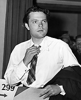 """Orson Welles following the U.S. Army physical examination <br /> <br /> Orson Welles, the one-man movie studio, adjusts his tie after the Army gave him a going-over and judged him """"4-F"""" at the Los Angeles induction center. The actor-director-radio artist explained he has a """"chronic and progressive back ailment.<br /> <br /> 7 May 1943"""