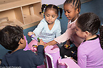Education preschool child care program 3-4 year olds 3 girls and a boy playing with dolls and a plastic castle