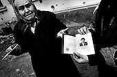 Grozny, Chechyna.1995.A woman who has survived the bombing of Grozny in her basement displays photographs of her two dead sons killed in the fighting.