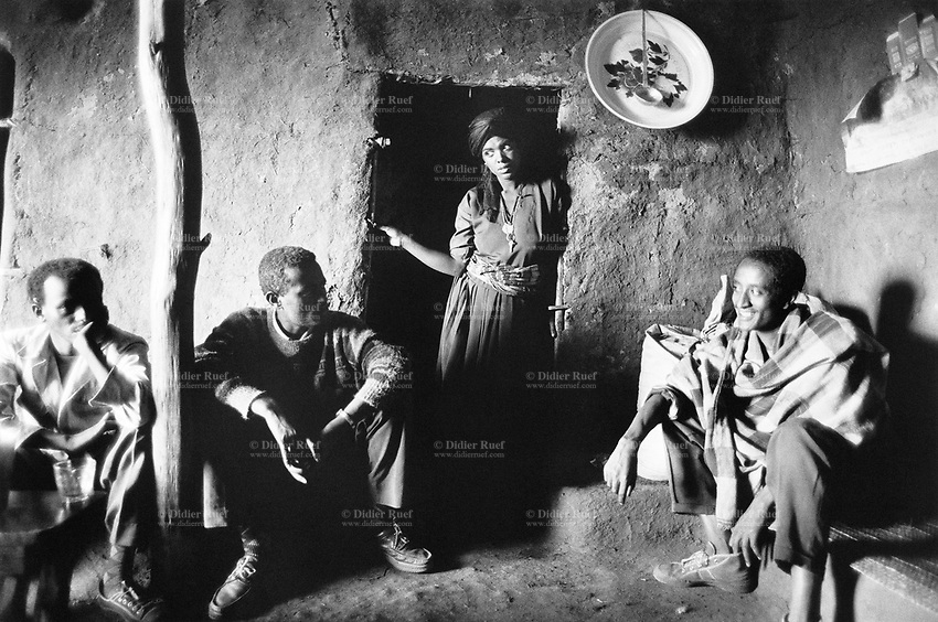 Ethiopia. West Gujam. Danbecha district. Anjeni is a small village. A group of men sit in a tiny coffee-house while the waitress stands up and waits for the order. The walls of the house are made of mud. © 1996 Didier Ruef