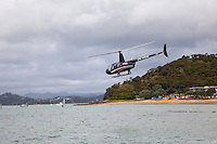 Helicopter Offering Sightseeing Rides over Paihia Bay, Paihia, north island, New Zealand.