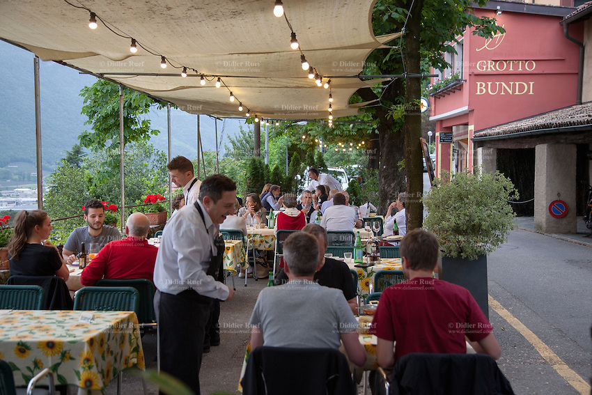 Switzerland. Canton Ticino. Mendrisio. Three waiters working at Antico Grotto Ticino serve tourists and local people enjoying traditional meals in a cosy atmosphere. The Grotto Bundi is the next restaurant on the road. 14.05.2015 © 2015 Didier Ruef