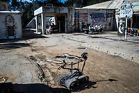 """A so called 'Packbot"""" is used by the Navy's bomb detection unit during training to diffuse IEDs (Improvised Explosive Devices) durig a training exercise. The training facility,  located at Spawar (Space and Naval Warfare Systems Command) in San Diego, is meant to resemble a village in the Middle East. Spawar is a research and operations arm of the Navy. The Unmanned Systems Group at Spawar is developing autonomous vehicles for the military, which they think will revolutionise the way the military fights. The challenge is to develop autonomous vehicles sturdy enough to operate in environments where there are no roads."""