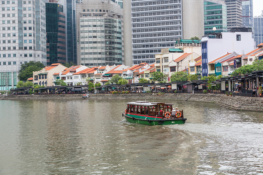Water taxi on Singapore River. Boat Quay, Former Shop Houses now Restaurants and Bars.  Buildings of the Financial District in background.  Singapore.