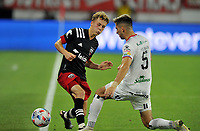 WASHINGTON, DC - JULY 7: Yurguin Roman #5 of Liga Deportiva Alajuense battles for the ball with Griffin Yow #22 of D.C. United during a game between Liga Deportiva Alajuense  and D.C. United at Audi Field on July 7, 2021 in Washington, DC.