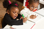 Education preschool 2-4 year olds art activity two girls drawing with markers younger child using a fist grip and talking to herself, older girl using a pencil grip tripod grasp