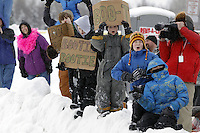 Saturday, March 3, 2012  Young fans hold signs requesting dog booties near the Alaska Native Hospital along the Ceremonial Start route of Iditarod 2012 in Anchorage, Alaska.