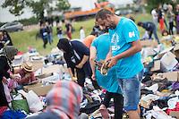Wilkommensfest fuer Fluechtlinge im saechsichen Heidenau.<br /> Nachdem Polizei und politisch Verantwortliche vergeblich versucht hatten ein Wilkommensfest fuer Fluechtlinge mit dem Argument des Polizeilichen Notstands zu verbieten feierten hunderte Menschen zusammen. Fuer die Fluechtlinge waren Kleidungs- und Sachspenden nach Heidenau gebracht worden, die in Berlin, Dresden und anderswo gesammelt wurden (im Bild).<br /> Zahlreiche Polizeikraefte waren zum Schutz des Festes im Einsatz.<br /> 28.8.2015, Heidenau<br /> Copyright: Christian-Ditsch.de<br /> [Inhaltsveraendernde Manipulation des Fotos nur nach ausdruecklicher Genehmigung des Fotografen. Vereinbarungen ueber Abtretung von Persoenlichkeitsrechten/Model Release der abgebildeten Person/Personen liegen nicht vor. NO MODEL RELEASE! Nur fuer Redaktionelle Zwecke. Don't publish without copyright Christian-Ditsch.de, Veroeffentlichung nur mit Fotografennennung, sowie gegen Honorar, MwSt. und Beleg. Konto: I N G - D i B a, IBAN DE58500105175400192269, BIC INGDDEFFXXX, Kontakt: post@christian-ditsch.de<br /> Bei der Bearbeitung der Dateiinformationen darf die Urheberkennzeichnung in den EXIF- und  IPTC-Daten nicht entfernt werden, diese sind in digitalen Medien nach §95c UrhG rechtlich geschuetzt. Der Urhebervermerk wird gemaess §13 UrhG verlangt.]