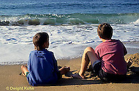 ON03-032z  Ocean - boys sitting on sandy beach watching waves breaking