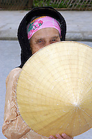 Shy, Elderly Vietnamese woman hold hat in front of face as she poses.