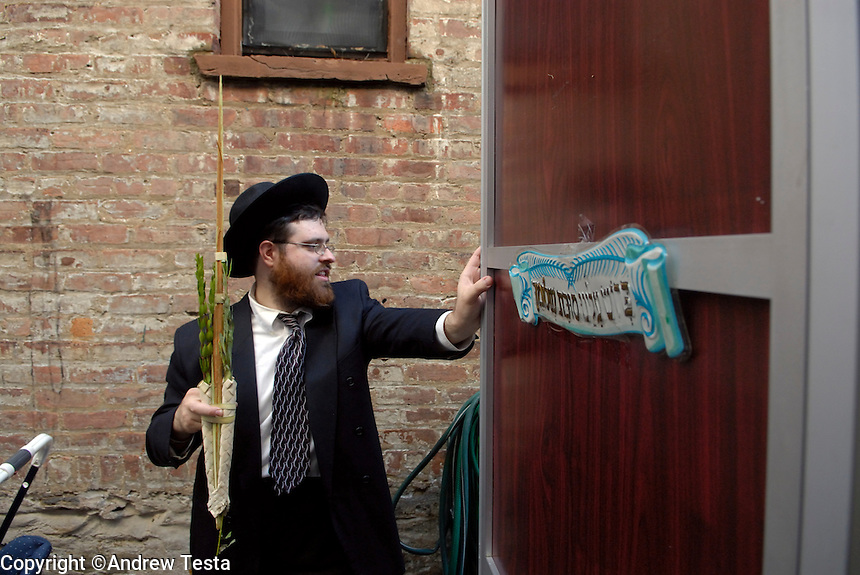 USA. Brooklyn. 10th October 2006..Rabbi Chaim Goldberg eats a fish breakfast with his family in their Sukkah, which he built in their driveway..©Andrew Testa