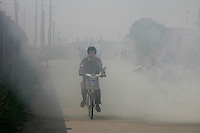 A man rides his bike through a thick cloud of smoke in Danyang, Jiangsu Province, China..19 May 2006