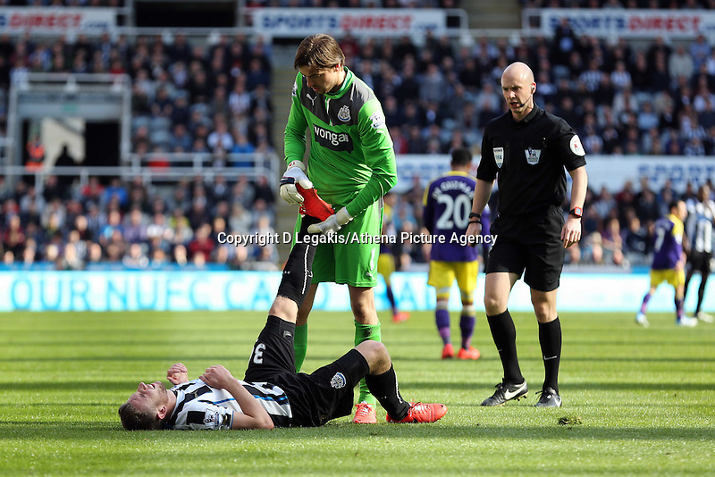 Pictured: Newcastle goalkeeper Tim Krul helps team mate Mathieu Debuchy with his leg cramp. Saturday 19 April 2014<br /> Re: Barclay's Premier League, Newcastle United v Swansea City FC at St James Park, Newcastle, UK.