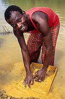 Tortiya, Ivory Coast (Cote d'Ivoire).  Malian Sifting for Diamonds in a Small Stream.