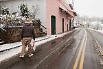A man shovels snow by the historic 1850s Chichizola Store along Jackson Gate Road, snow.