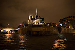 A view of Le Notre Dame from the stern of a 1950,s era river yacht  floating down the Seine river on a January evening in Paris France, This image shows a  dramatic view of the flying buttresses, stone walls and water surrounding the historic catholic church.