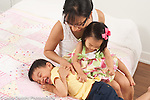 3 year old boy getting tickled by 18 month old baby sister held by mother