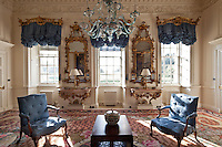 William Mathie gilt-wood mirrors (1759) and George Mercer console tables make a grand display between the ruched blue curtains  of the drawing room windows