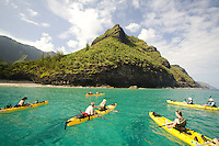 Sea kayakers paddling down Kauai's Na Pali coast in a group tour