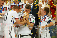 Thomas Muller of Germany celebrates winning the FIFA World Cup by kissing the trophy