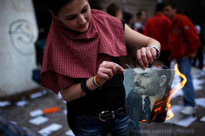 A young Moldovan girl lights a portrait of Vladimir Lenin on fire after rioters took the portrait from inside the Parliament building in Chisinau, Moldova on 7 April 2009. Opposition leaders accused the Communists of rigging the elections on 5 April and demanded a recount. Anti-communist rotesters stormed the presidential building, demanding that President Vladimir Voronin announce his resignation and leave Moldova. More than 30 people were injured in the protests.