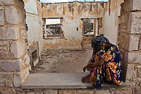 "A woman resting in an archway of ""STATE HOUSE""..A brutal campaign of repression by Siad Barre's regime led to civil war in Somalia in 1988.  Hundreds of thousands of people fled for their lives.  Somalilanders fought for their independence and as one of the key battlegrounds, Hargeisa was all but destroyed.  Its people returned in 1992 to find their homes destroyed, their livelihoods gone and nowhere to go in a city they had previously called their own.      ..Many settled in waves in the bombed out building and grounds of State House...Built in 1952 in anticipation of a visit by Queen Elizabeth II, State House was the jewel in British Somaliland's crown - host to dignatories and home to the Governor of the Protectorate who would entertain on its golf course and in its gardens.  ..29,000 people now call State House home.  Amongst the barren landscape, flimsy shelters, broken glass, rusty nails and in the derelict shadow of the former State House has sprung a city.  Its people are both legacy and testament to wars gone by and current conflict in Somalia.  ."
