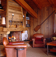 A pair of leather armchairs beside the cosy fire in the double-height living room of the chalet