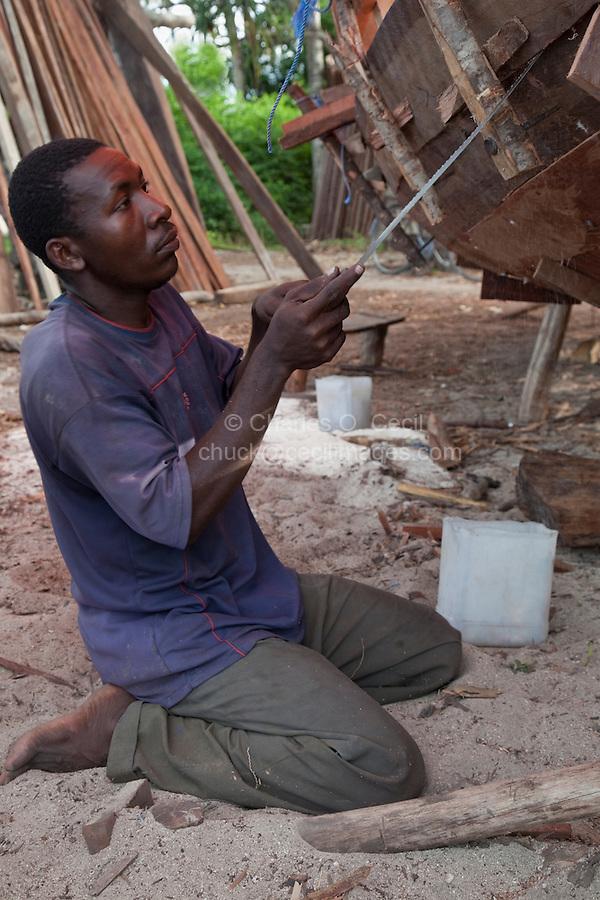 Zanzibar, Tanzania.  Carpenter Building a Dhow.  Sawing to make a better fit.