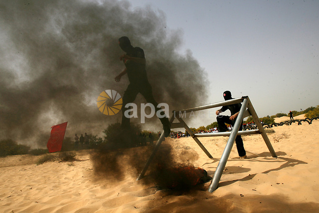 Palestinian militants of the Popular Front for the Liberation of Palestine (PFLP) demonstrate their skills during a military graduation ceremony in front of the media in Khan Younis in the southern Gaza Strip March 13, 2013. Photo by Eyad Al Baba