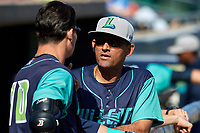 Lynchburg Hillcats manager Rouglas Odor (24) talks with Mitch Longo (10) in the dugout before the first game of a doubleheader against the Frederick Keys on June 12, 2018 at Nymeo Field at Harry Grove Stadium in Frederick, Maryland.  Frederick defeated Lynchburg 2-1.  (Mike Janes/Four Seam Images)
