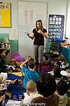 Education Elementary school Grade 2 female teacher talking to group on rug vertical