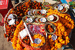 A display of offerings for pilgrims to purchase to offer to the holy River Ganges, including garlands of marigolds, incense, sweets, and small bowls made from dried leaves with a candle inside. These leaf bowls are increasingly made from tin foil, and there is growing concern around pollution of the river.