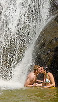 A young couple sneaks a kiss under the rushing waterfall of Waimea Falls.