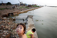 Children playing on the shores of Dongting Lake, Hunan Province. Dongting Lake has decreased in size in recent decades as a result of land reclamation and damming of the Yangtze. China. 2010