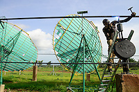 BURKINA FASO, Dano, foundation Dreyer, rice mill with solar cooker, steam is produced by parabolic mirror to process paddy, skilled worker with welding torch at water pipe system / BURKINA FASO, Dano, Stiftung Dreyer, Reismuehle mit Solaranlage mit Parabolspiegeln zur Dampferzeugung fuer Reisverarbeitung, Facharbeiter bei Schweissarbeiten am Wasserrohrsystem