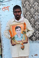 INDIA Maharashtra, farmer Prafull Ramdasji Wankhede with the picture of his died brother Prabhu Ramdasji Wankhede, who has committed suicide due to high debt and cotton crop failure in Vidarbha region / INDIEN Maharashtra, Region Vidarbha , Dorf Sonegaon, Baumwollfarmer Prafull Ramdasji Wankhede mit dem Foto seines verstorbenen Bruders Prabhu Ramdasji Wankhede, der nach Missernte und hoher Verschuldung Selbstmord begangen hat